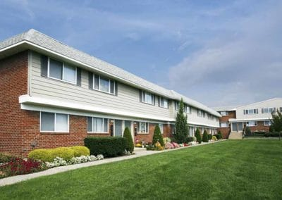 Exterior of brick and grey siding apartment building with landscaping featuring plants and flowers and a well-manicured lawn
