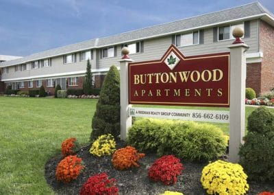 Red sign with gold lettering for Buttonwood Apartments with floral landscaping