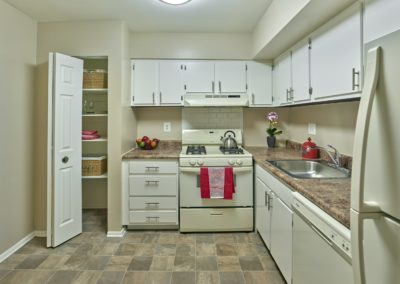 Large kitchen with white cabinets, white appliances, and a pantry closet in apartment rental