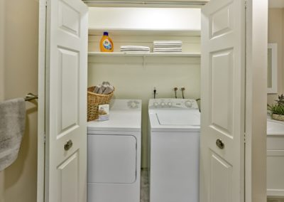 Side by side washer and dryer in laundry closet with shelving