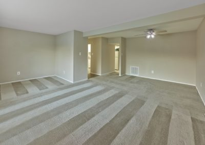 Large carpeted living room with ceiling fan at apartment for rent in Medford, NJ