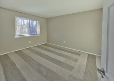 Spacious bedroom with new carpet and large window in apartment for rent