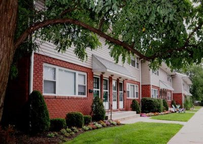 Exterior of apartment building with red brick, beige siding, awnings over doors and beautiful landscaping