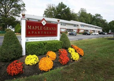 Red and white property sign for Maple Grand Apartments surround by freshly cut grass, bushes, and mums