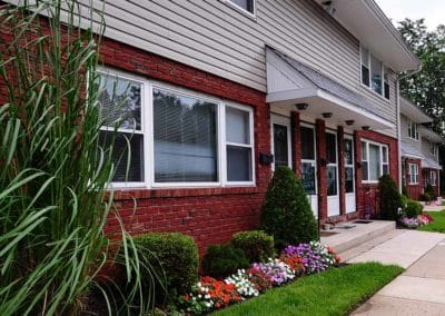 Exterior of Maple Shade, NJ apartment building with brick and beige siding and well-kept grass and flowers