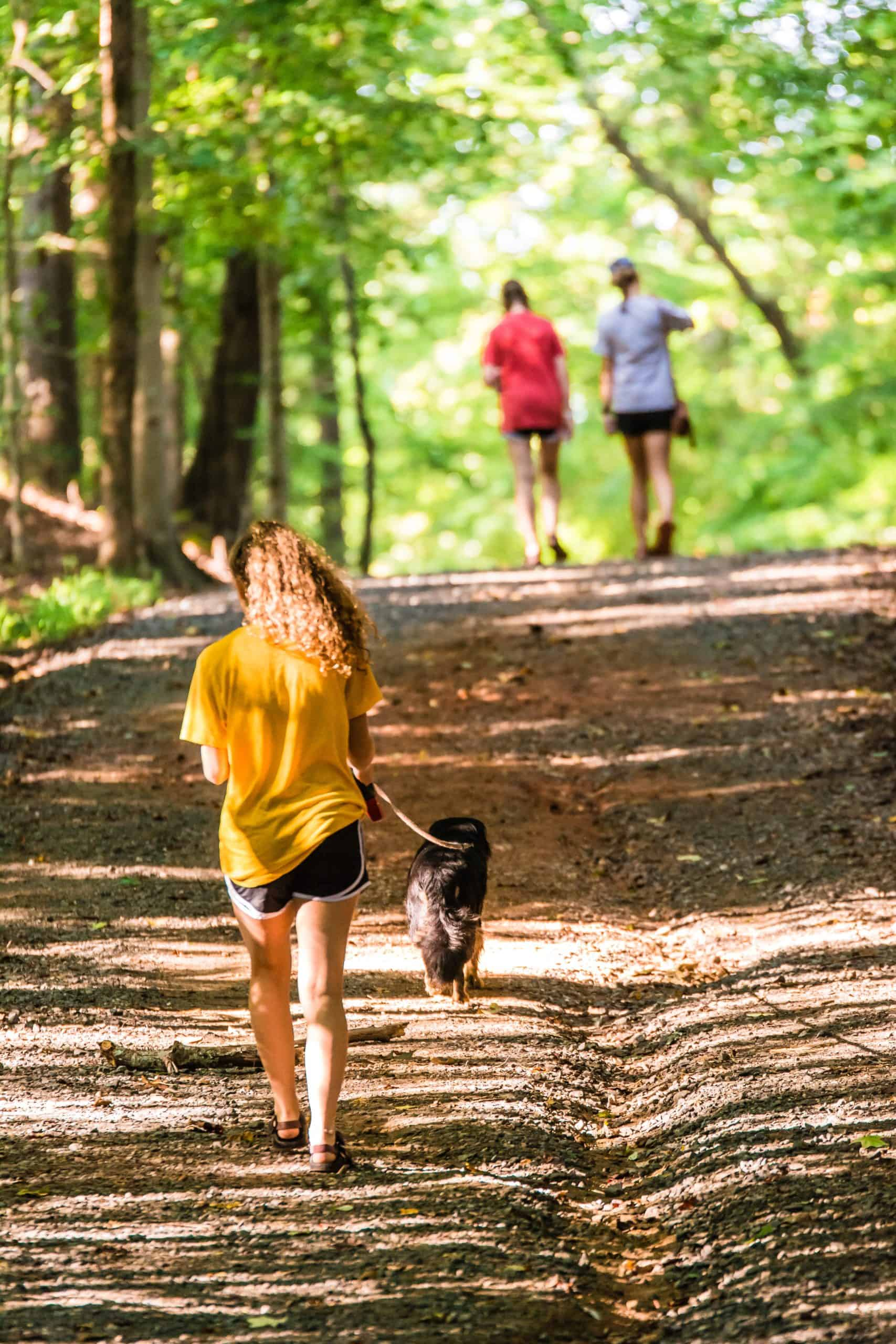 girl hiking in woods with dog on leash