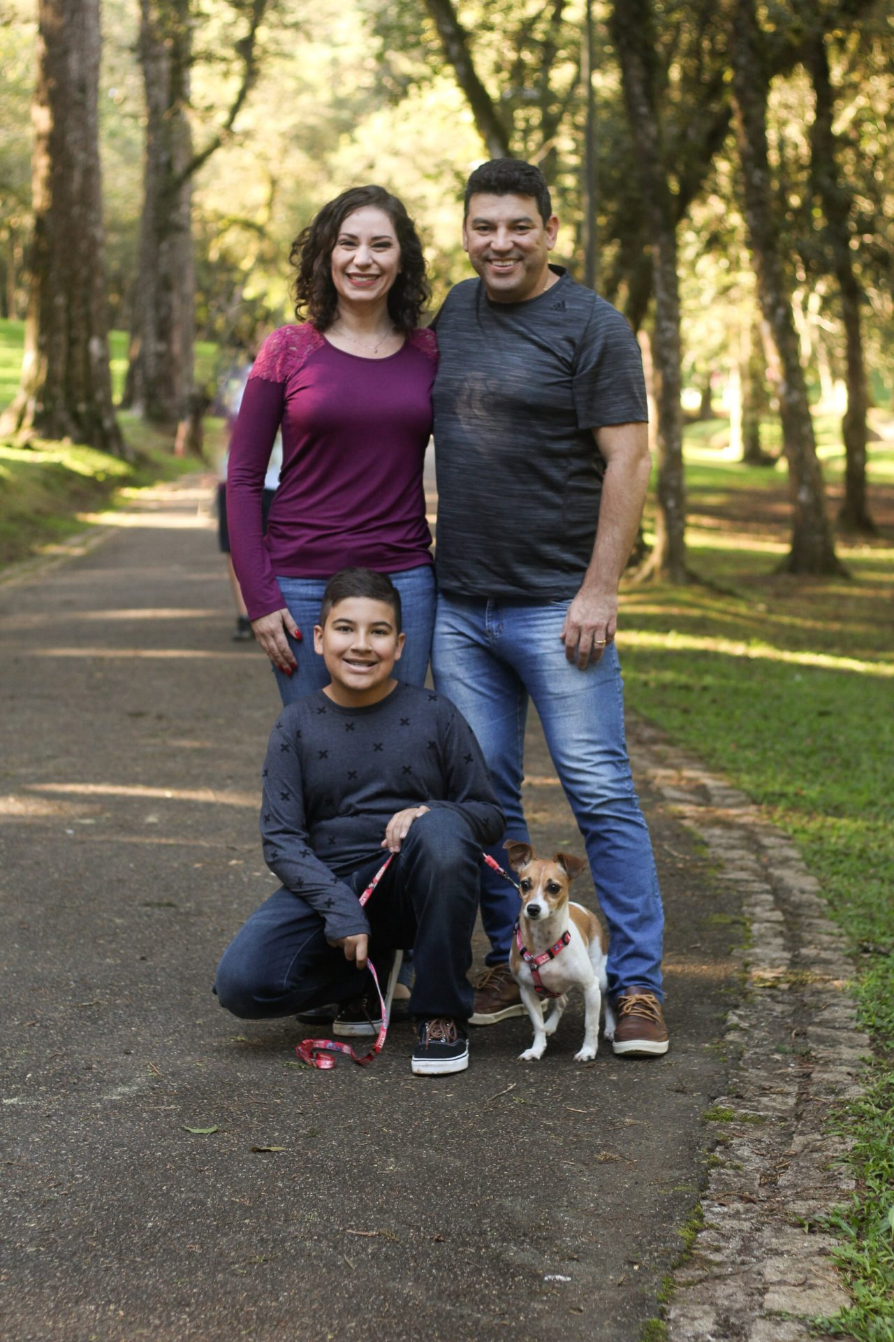 three people with dog at park