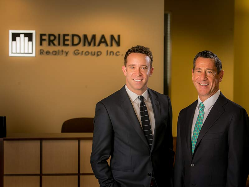 David and Brian Friedman posing for a photograph at the Friedman Realty Group offices