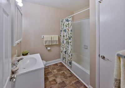 Contemporary bathroom with white sink and vanity and medicine cabinet at Maple Grand Apartments