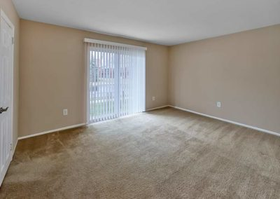 Huge carpeted bedroom with sliding doors leading to outside patio