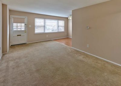 Spacious, carpeted living area with external door, large window, and beige colored walls