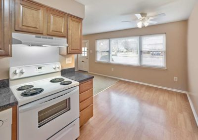 Updated kitchen with vinyl flooring, lightwood cabinets, and white appliances with space for a dining area