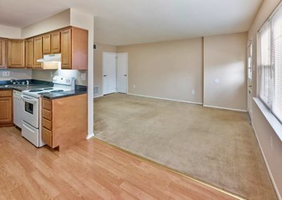 Spacious hardwood kitchen looking into carpeted living space with large window