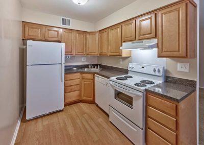 Kitchen with white appliances, corner sink, dark countertops, and plenty of space