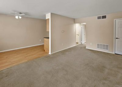 Open space in apartment for rent in Maple Shade, NJ with large carpeted area leading in to a hardwood floored dining area with ceiling fan