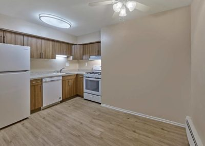 Renovated kitchen with hardwood vinyl flooring, white appliances, and wood cabinets