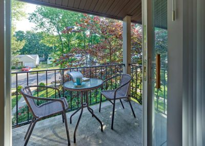 Table and chairs on private balcony shown through open sliding glass door