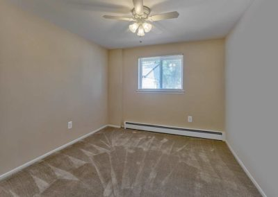 Moderate sized bedroom with carpeting, a small window, and ceiling fan
