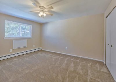 Carpeted bedroom with large window, ceiling fan, and spacious closet at apartment for rent in Somers Point, NJ