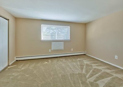 Spacious, carpeted bedroom with large window and plenty of outlets