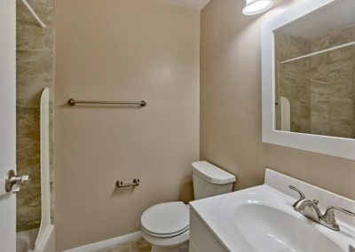arge bathroom with white sink and vanity and stone tile in modern shower