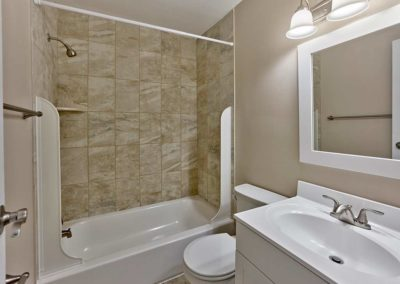 Floor to ceiling stone tiling on wall of bathtub and shower in large contemporary bathroom