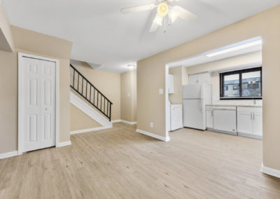 Newly renovated dining area with vinyl flooring, ceiling fan, and white trim leading in to kitchen