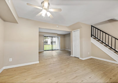 Spacious living room with ceiling fan in to large dining room with sliding doors out to patio, a stairway on the right and vinyl flooring throughout