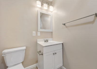 First floor half bathroom in a Mystic Point Townhome with small white vanity and mirror