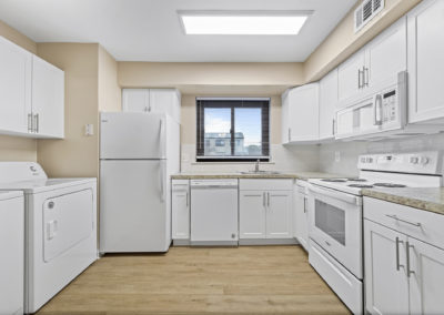 Brand new kitchen with white modern cabinets, white appliances, vinyl floors, and an in-unit washer and dryer