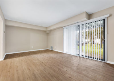 Beautiful, large sliding glass doors bringing in lots of natural light to large living space with hardwood flooring