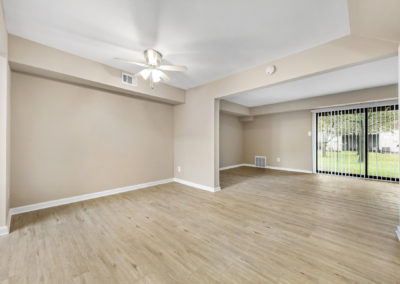 Large apartment living and dining area with vinyl flooring and sliding glass doors leading outside to a patio