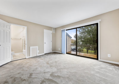 Beautiful master bedroom with balcony, walk-in closet, and cozy carpeting at Mystic Point Townhomes