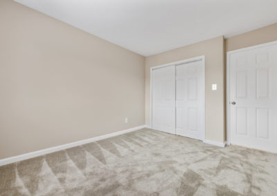 Spacious master bedroom with carpeting and large closet