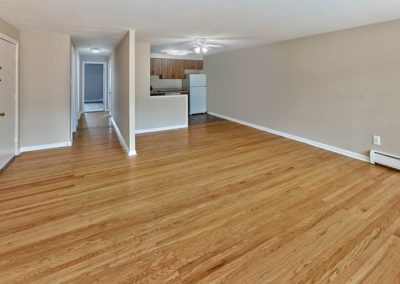 Spacious living room with hardwood flooring and plenty of natural light from large windows