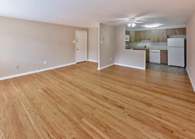 Living room and front entrance to Darby Creek Apartments with hardwood flooring and neutral colored walls