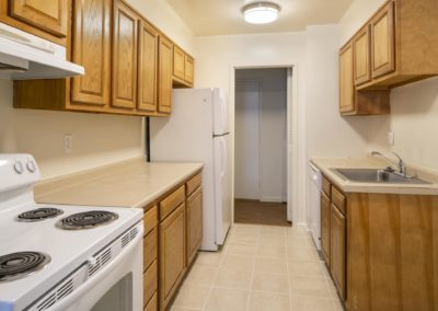 Apartment galley kitchen wood cabinets, tile floor and white appliances