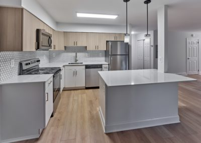 Renovated apartment kitchen with white cabinets, hardwood floors, and an island