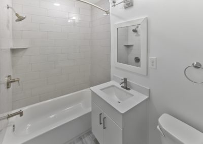 Renovated apartment bathroom with white sink and vanity and contemporary tiled shower