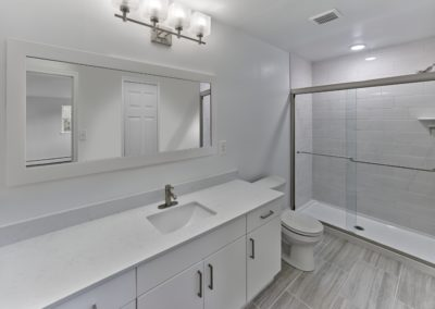 Large handicap accessible apartment bathroom with huge vanity and walk-in shower