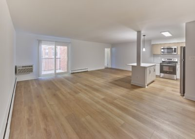 Renovated apartment living space with hardwood flooring, open floor plan, and sliding glass doors