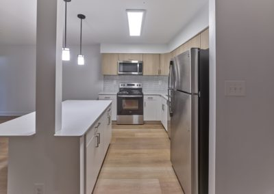 Renovated apartment kitchen with stainless steel appliances, white cabinetry, and a kitchen island