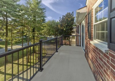 Private balcony outside of Wayne, PA apartment for rent with sunny view and black railing