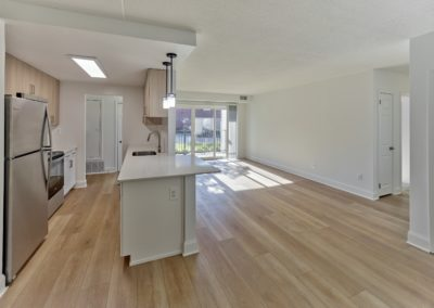 Open concept kitchen and living area with hardwood flooring in renovated Wayne, PA apartment for rent