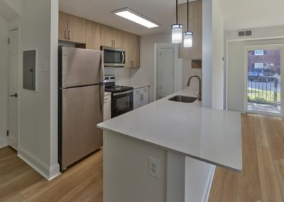 Gorgeous, renovated apartment kitchen with stainless steel appliances, a breakfast bar, and overhead lighting