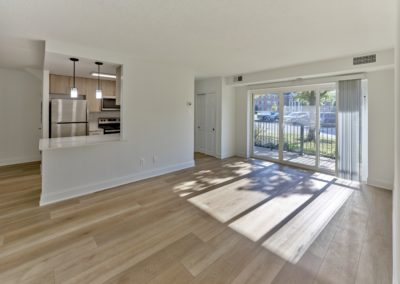 Open concept living area in Wayne, PA apartment for rent with hardwood flooring and sliding doors out to private balcony