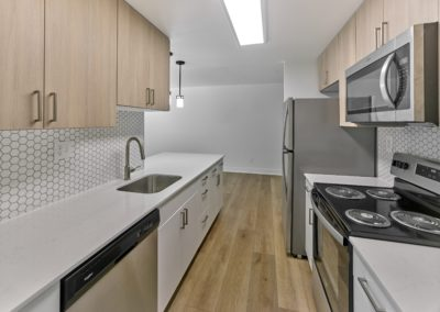 Renovated galley kitchen with two-tone cabinets, stainless steel appliances, and hardwood flooring