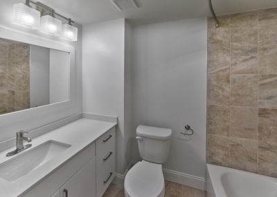 Renovated apartment bathroom with large vanity and tiled shower