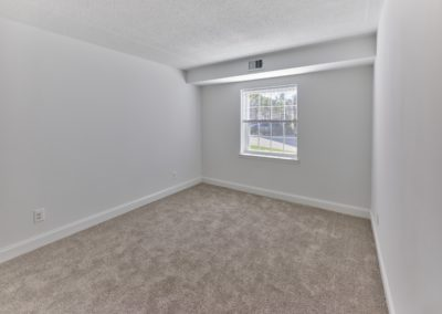 Spacious bedroom with plush carpeting and a large window