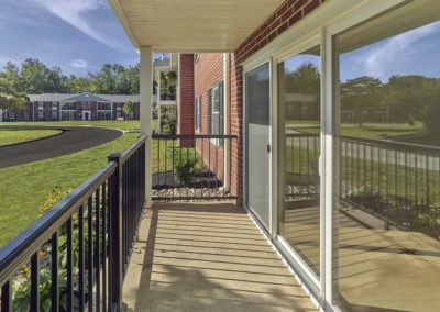 Private balcony with sunny view and black railing outside of apartment for rent in Wayne, PA